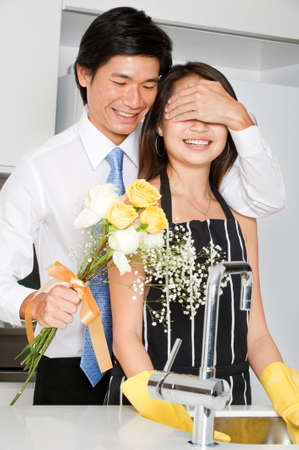 good looking man: A good looking man surprising his wife with a bouquet of flowers at home Stock Photo