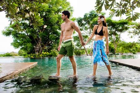 bikini couple: An attractive young couple in swimwear walking by a pool outdoors Stock Photo