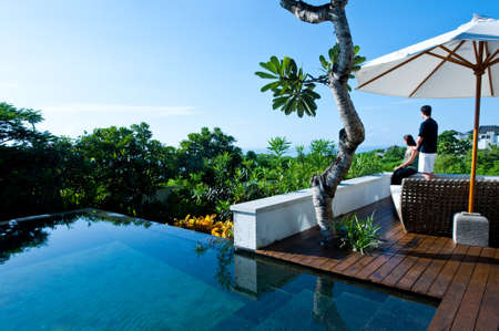 An attractive young couple relaxing by the pool outdoors Standard-Bild