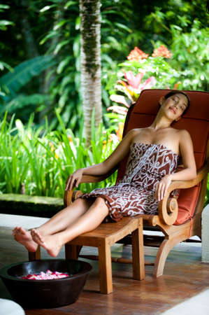 lounging: An attractive young woman relaxing at a spa outdoors