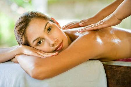 Eine attraktive junge Frau, die eine Rückenmassage auf ein Spa im Freien genießen  Standard-Bild