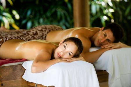 Eine attraktive junge paar auf massage Betten auf ein Spa im freien