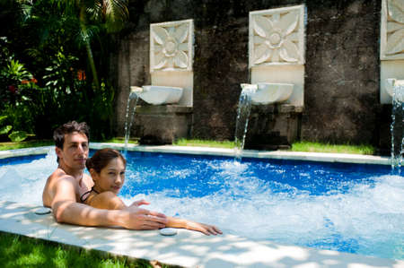 An attractive young couple in a jacuzzi pool outdoors Stock Photo