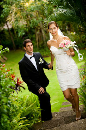 An attractive young bride leading her groom up stone steps outdoors photo
