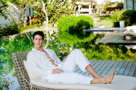 lounging: An attractive man lounging on a daybed outdoors