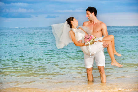 An attractive bride and groom getting married by the beach photo
