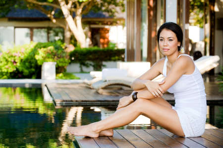 An attractive caucasian woman relaxing on a deck by the pool outdoors photo