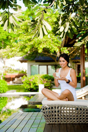 An attractive caucasian woman relaxing with a drink outdoors photo