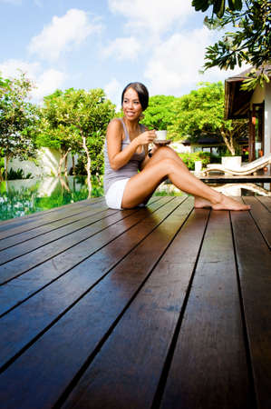 An attractive caucasian woman relaxing with a drink outdoors Standard-Bild
