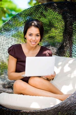 An attractive caucasian woman relaxing and using her laptop outdoors photo