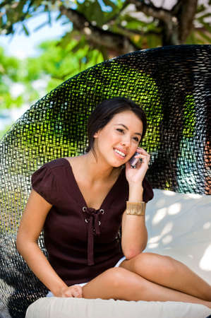 An attractive caucasian woman talking on her mobile phone outdoors photo
