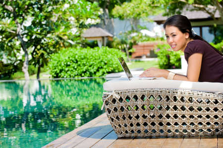 An attractive caucasian woman relaxing and using her laptop outdoors Stock Photo - 6948310
