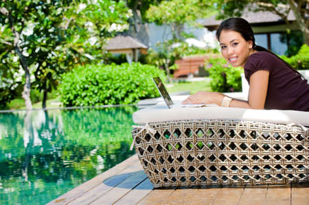 An attractive caucasian woman relaxing and using her laptop outdoors Stock Photo - 6782350