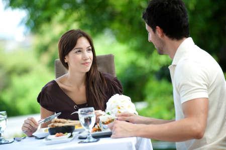 Eine attraktive caucasian paar eine entspannte Mahlzeit im freien zusammen mit