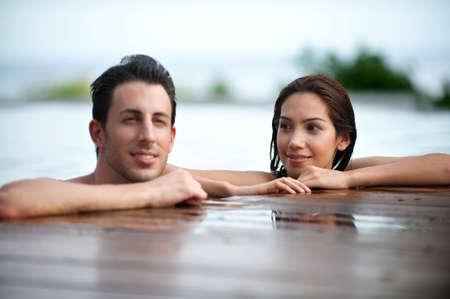 Eine attraktive caucasian paar entspannen in eine outdoor Pool zusammen