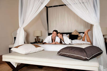 lounging: An attractive caucasian couple relaxing and lounging in their bedroom indoors Stock Photo
