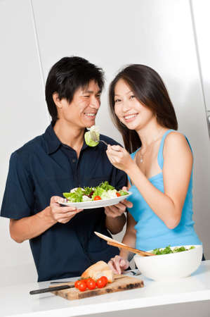 An attractive asian couple having a healthy salad in their kitchen at home photo