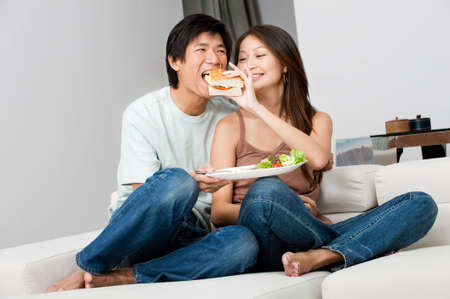 A good looking couple having a sandwich on their couch at home