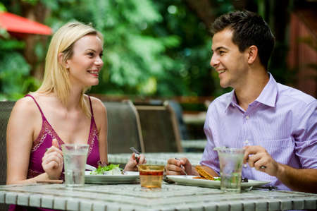 An attractive caucasian couple having a meal at an outdoor restaurant Standard-Bild