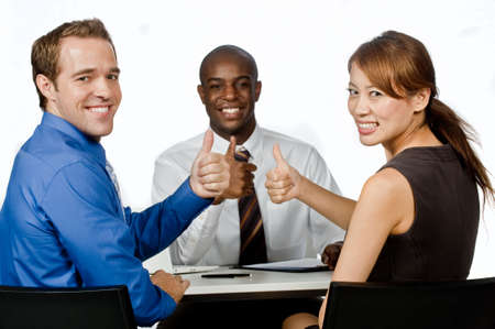 An attractive young group of business professionals giving the thumbs up in their office against white background photo