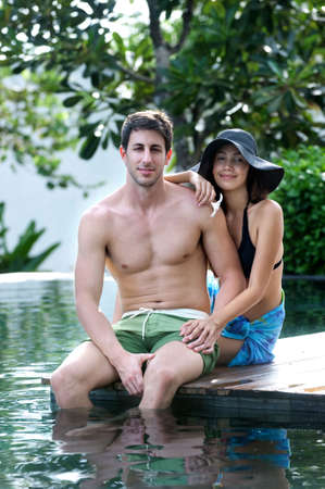 An attractive caucasian couple relaxing and lounging outdoors by a pool photo