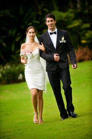 An attractive young bride and groom smiling at each other in a garden outdoors