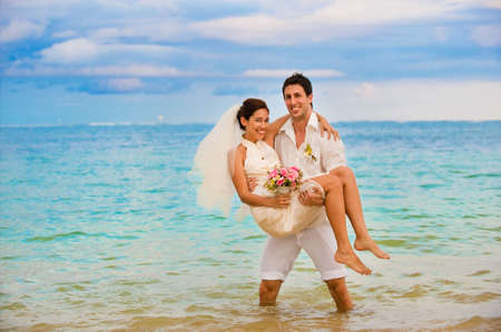 An attractive caucasian couple getting married by the beach photo