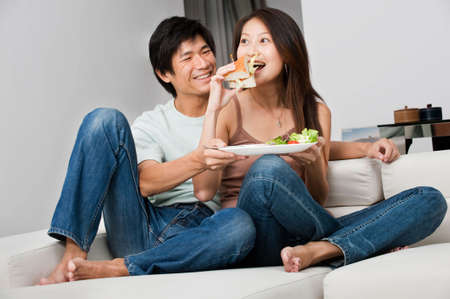 A good looking couple having a sandwich on their couch at home photo