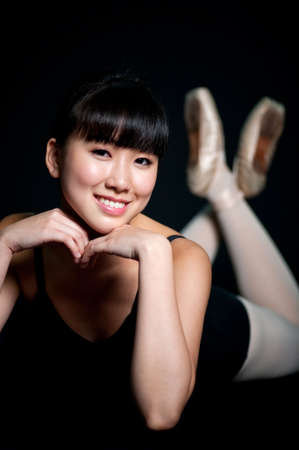 A young asian ballerina posing with her chin on her hands, against black background photo