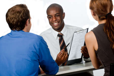 A young and professional businessman having a discussion with two of his colleagues on white background photo