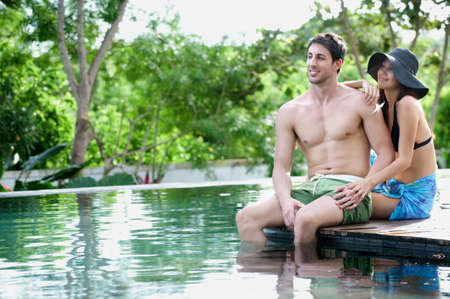An attractive caucasian couple relaxing and lounging outdoors by a pool
