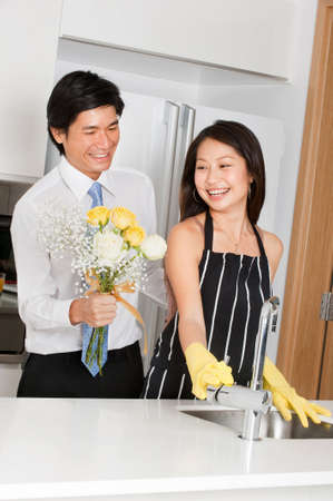 good looking man: A good looking man giving a bouquet of flowers to his wife at home