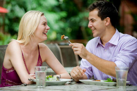 An attractive caucasian couple having a meal at an outdoor restaurant Stock Photo