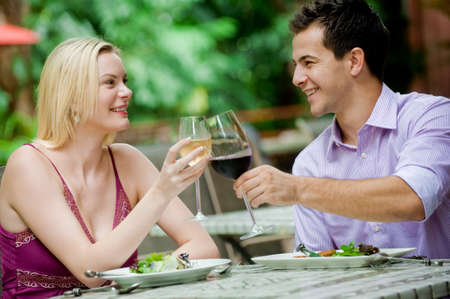 An attractive caucasian couple having a meal with wine at an outdoor restaurant Stock Photo - 6925516