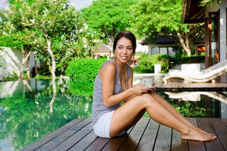 Eine attraktive junge Frau, die im freien mit einem Drink entspannen