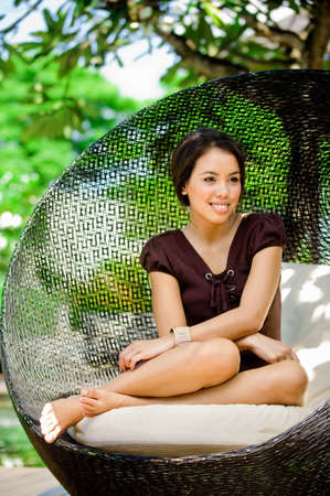 lounging: An attractive young woman relaxing and lounging outdoors