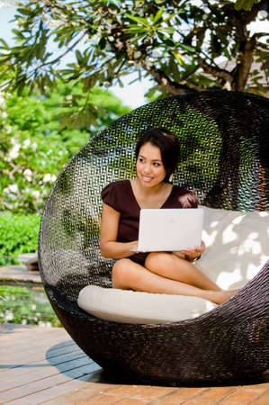 An attractive young woman using her laptop outdoors photo