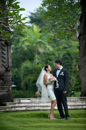 Attractive caucasian newly weds getting married outdoors in a garden Standard-Bild