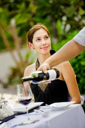 An attractive caucasian woman having red wine with her meal outdoors
