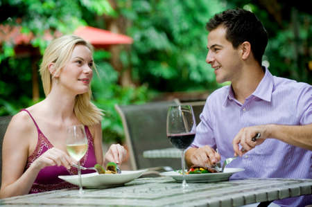 outdoor restaurant: An attractive caucasian couple having a meal with wine at an outdoor restaurant Stock Photo