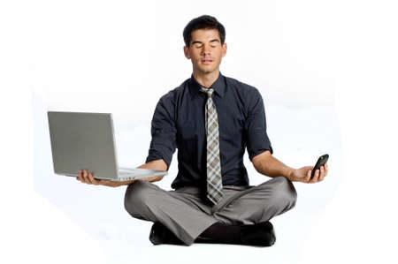 An attractive athletic businessman doing a yoga pose while using his mobile phone and laptop against white background Standard-Bild