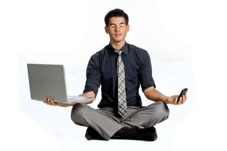 Eine attraktive athletic Geschäftsmann tun eine Yoga-Pose während der Verwendung von seinem Mobiltelefon und Laptop gegen weißen Hintergrund
