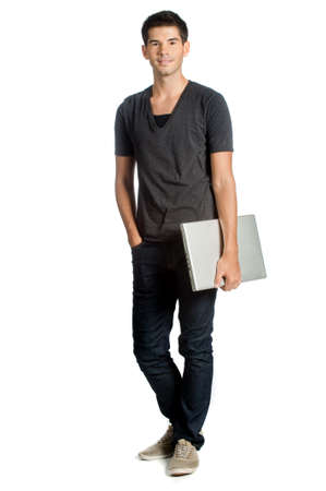 good looking man: A good looking man holding his laptop and standing against white background