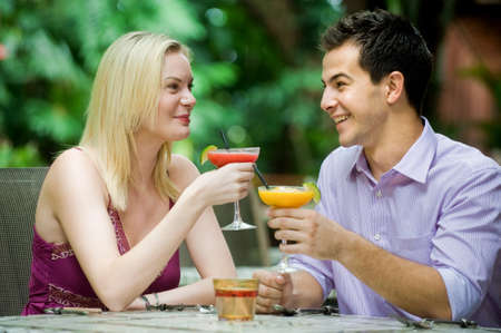 An attractive caucasian couple having drinks and relaxing at an outdoor restaurant photo