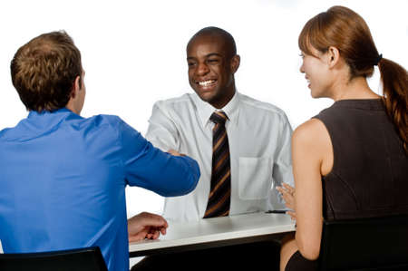 deal in: A young and professional businessman shaking hands and securing a deal in his office