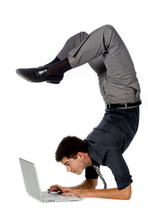 An attractive athletic businessman doing a handstand while using his laptop against white background