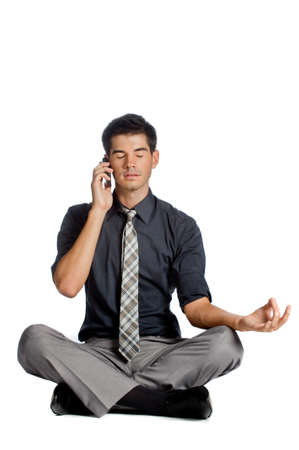 An attractive athletic businessman doing a yoga pose while using his mobile phone against white background