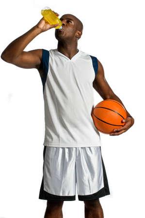 Eine attraktive athletic Mann mit einer Basketball trinken ein Energy-Drink vor weißen Hintergrund