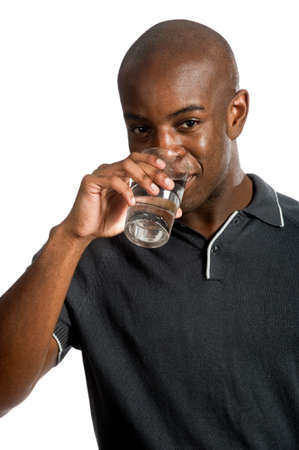 An attractive man drinking a glass of water against white background photo