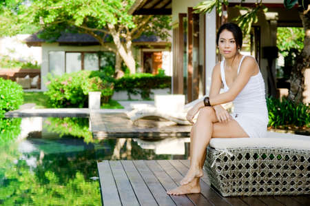An attractive young woman relaxing outdoors by the pool photo
